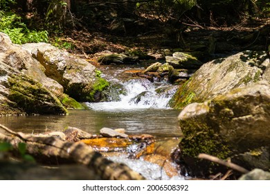 view of the waterfalls of a smaller river bordered by stones