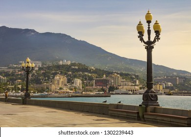 View from the waterfront, decorated with ancient lanterns, on Central Yalta and the surrounding mountains.Crimea.