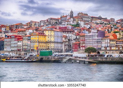 A view of the waterfront promenade on the Douro River with the city of Porto in Portugal  rising up on the hills behind.