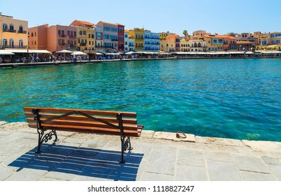view of waterfront promenade with tourists, bars, hotels and restaurants in central historic part of Chania on sunny summer day, Crete, Greece