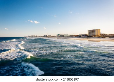 View of waves in the Atlantic Ocean and the beach from the pier in Daytona Beach, Florida.