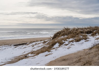 View of waves crashing into the beach at sunset, during the winter with snow on the sand dunes, in Montauk