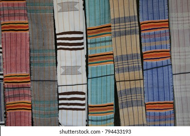 View of weaved tissue bands from ivory coast. Colorful traditional clothes suspended. Handicraft and souvenirs from Grand Bassam near abidjan. Vertical and horizontal lines. Soft textile texture.