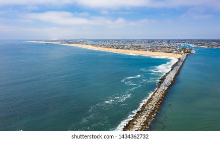 View of the Wedge down the seawall of Newport Beach Harbor