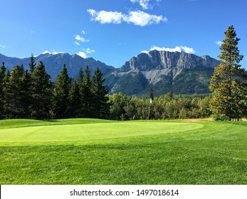 A view of a well manicured golf green with trees and the rocky mountains in the background.  It is a beautiful sunny day playing golf in Kananaskis.
