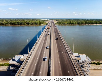 A view to the well-built city bridge across the river. City river gates. Trasportation across the river at the forest and horizon background. Vehicular traffic on the highway across the river