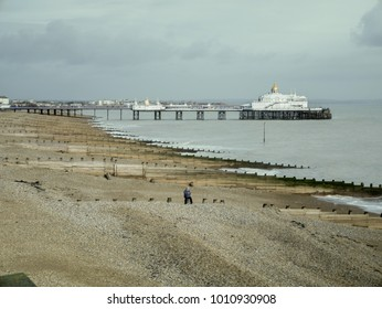 A view from the west side of Eastbourne Pier with a guy sitting on a wooden post in the far distance and Eastbourne Pier behind him. Blue sky's and pebbles.