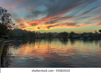 View of Westlake Village lake at dusk with sunset reflections on the water; soft focus