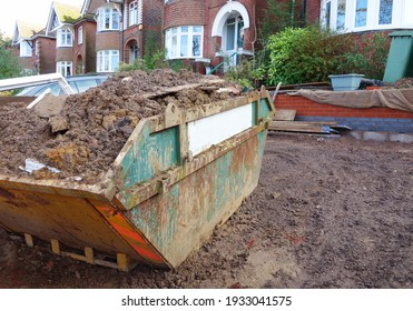 View of wet ground work and some earth put in big industrial skip, one side of frame. Space to add text on blurry wet mud and slope garden floor. Home building, renovating, waste removing concept.