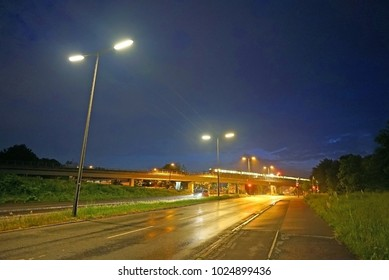 View of wet night road illuminated by street lights