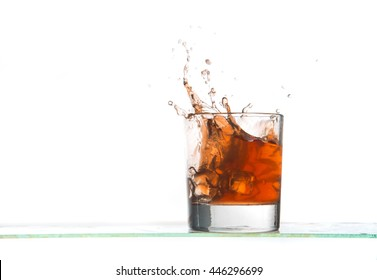 View of whiskey glass with ice cubes and drink splash on white background.