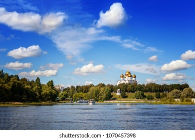 View of the white church with golden domes on the river bank against the blue sky, Yaroslavl, Russia. Landscape.
