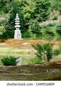 View of the White Snake Mound or White Snake Pagoda (Hakuja-no-Tsuka) of Kinkaku-ji. has four carved Buddhas at its base, located in the middle of Tranquility Pond (Anmintaku) at Kinkaku-ji temple