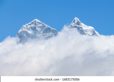 View of white snowy Kangtega mountain peak above clouds in Himalayas during the day on the way to Everest base camp in Nepal. Clear blue sky. Theme of beautiful mountain landscapes.