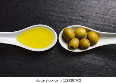 VIEW OF WHITE SPOONS WITH OLIVES AND OLIVE OIL