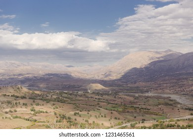 View of a wide area full of fields and small mountains with a blue sky with clouds and warm sunlight creating cloud shadows underneath