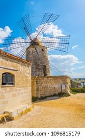 View of a windmill in the Saline di Trapani e Paceco natural reserve near Trapani, Sicily, Italy