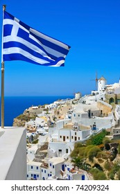 View of windmills with Greece flag in Oia village on island of Santorini, Greece