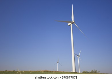 View of windmills towers from the ground with a cloudless blue sky.