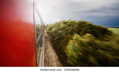 View from the window of a commuter train with motion blur and sunlight shining through the clouds.