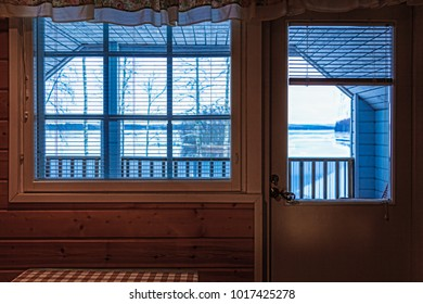 The view from the window of the cottage in winter landscape - lake and forest