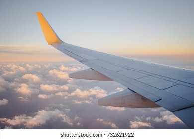 View of window at flying airplane, Plane wing on blue sky
