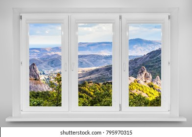 View from the window. Mountain forest landscape under evening sky with clouds in sunlight