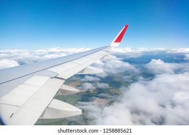 View from the window of the plane to the fields and clouds blue sky, air travel concept background