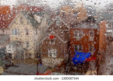 View from a window with raindrops to a row of houses