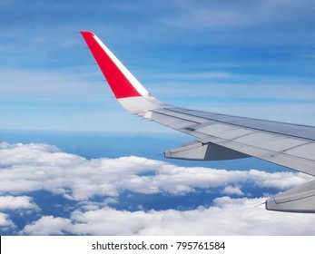 View from the window wing of airplane flying above the clouds.