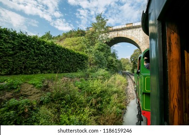 A view from window of wooden railway car of countryside, trees and grass along railway track, green and red steam engine riding through a valley under arch stone bridge, Czech Republic, Europe