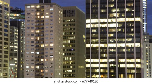 View of windows of high rise buildings at night, offices and apartments
