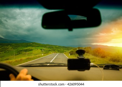 View from windscreen. Driving a car in Tuscany valley Valdorcia in stormy weather at sunset, Italy