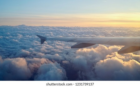 View from wing while flying over the clouds during sunset