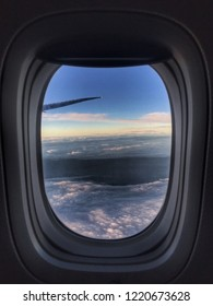 View of a winglet in the sky through an airplane window