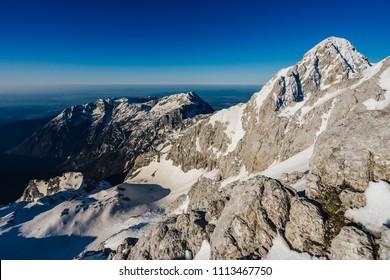View of a winter mountain alpine landscape of Kamnik Savinja Alps. Mount Skuta,Turska Gora and Rinka, Triglav in the background. Blue sky, perfect adventure day for outdoor activity like climbing.