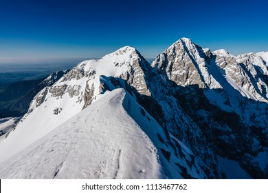 View of a winter mountain alpine landscape of Kamnik Savinja Alps. Mount Skuta,Turska Gora and Rinka, Triglav in the background. Blue sky, perfect adventure day for outdoor activity like climbing.