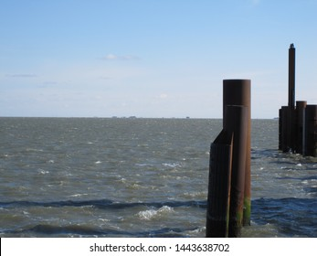 View from the Wittdun ferry terminal towards Hallig Langeness, dolphins (for mooring) in the foreground, blue sky with few clouds (Amrum, Schleswig-Holstein, Germany)