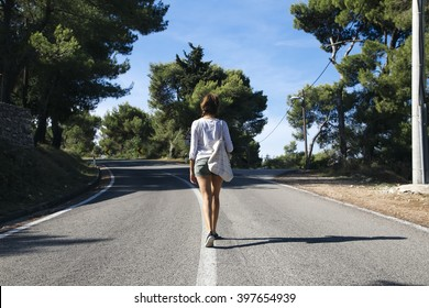 View of the woman from the back walking on the road