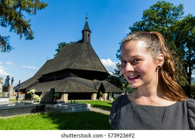 View of a woman in front of the ancient historic church Dreveny Goticky Kostol in Trvdosin, Slovakia - Shutterstock ID 573923692
