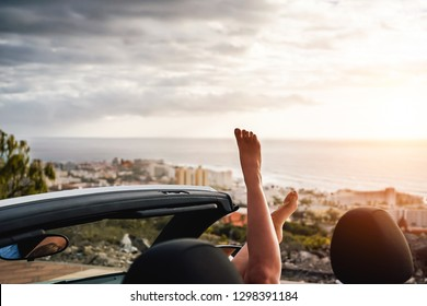 View of woman legs inside convertible car during a road trip - Young girl having fun traveling in cabriolet car in summer vacation - People, travel and youth lifestyle concept