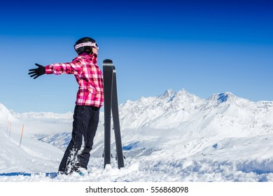 View of woman in mask standing and holding ski during sunny winter day