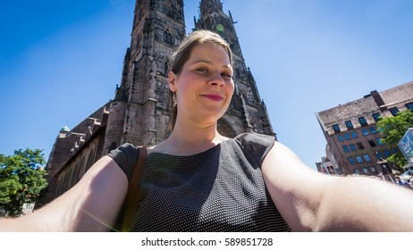 "View of woman taking selfie in front the ""Frauenkirche"" in Nuremberg"