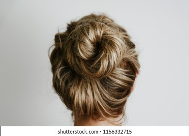 A view of the woman's hair from the back. Fashion and hairdressing concept. The girl, turned back, shows her hair bunched up in a bun on a light background.