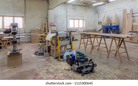 View of wood processing shop with windows, lamps, cables and crafting tables, lathe, portable milling machine, industrial vacuum cleaner and wood blanks on dirty floor