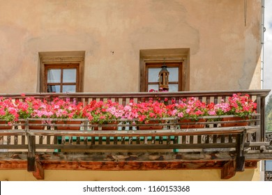 view of wooden balcony of traditional house covered with blossoming geranium flowers, shot on a bright summer day at Gressoney Saint Jean,  Lys valley, Aosta, Italy