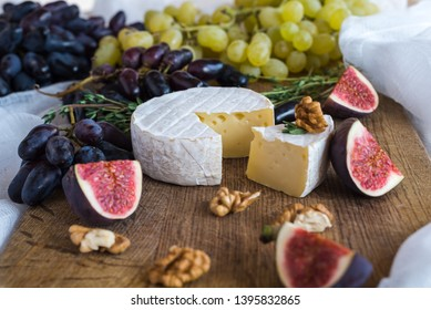 View of a wooden board with the head of white Camembert cheese and cut figs, nuts