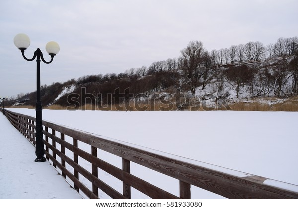 View of the wooden boardwalk on the lake in the village of AMBER in the winter