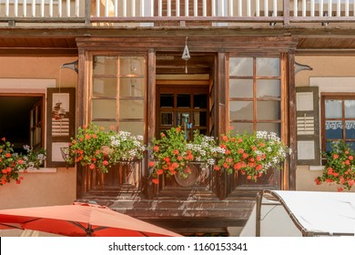 view of wooden bow-window of traditional house covered with blossoming geranium flowers, shot on a bright summer day at Gressoney Saint Jean,  Lys valley, Aosta, Italy