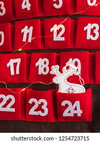 View of a wooden deer Christmas decoration in a pocket of a red Advent calendar with white numbers and Christmas lights. Christmas Eve concept